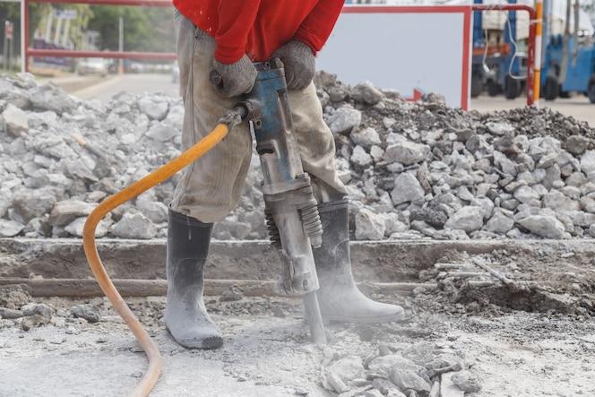 Trabajador que utiliza la construcción de cemento de perforación en el suelo