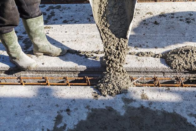 Trabajador que vierte la mezcla de concreto en la base de la casa