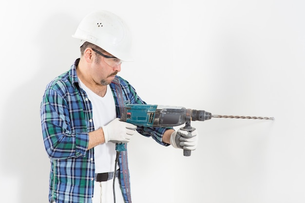 Trabajador reparador, con casco protector y gafas, perfora una pared blanca con un perforador