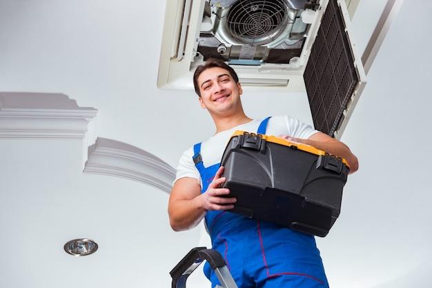 Trabajador reparando unidad de aire acondicionado de techo