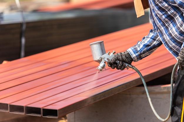 Trabajador rociando pintura a tubería de acero para evitar la oxidación en la superficie
