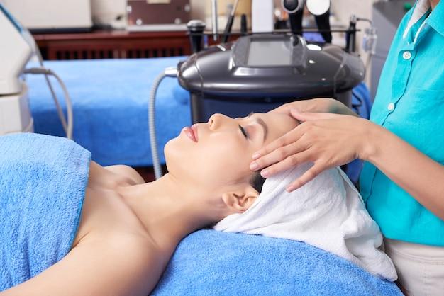 Trabajador de salón de spa dando masaje facial