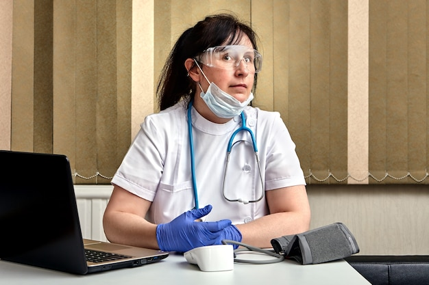 El trabajador de la salud está descansando en su oficina en el intervalo entre la recepción de pacientes durante la epidemia de infección por coronavirus covid-19.