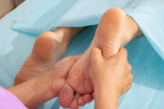 Trabajador sanitario dando masaje ortopédico a pies de hombre