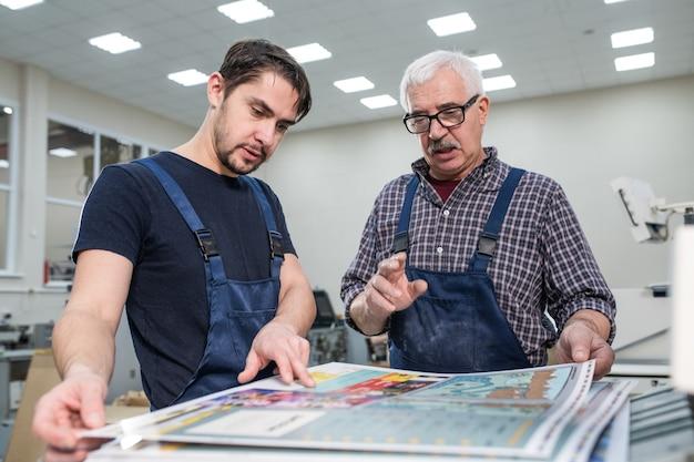 Trabajador senior experimentado en gafas explicando joven cómo estimar la calidad de impresión durante su pasantía