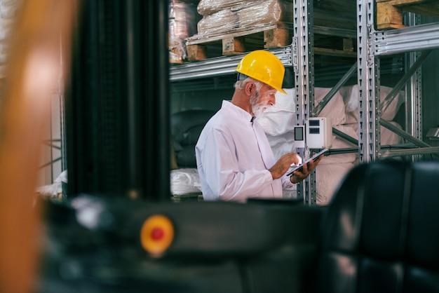 Trabajador senior en ropa de trabajo con tableta y control de temperatura en almacén.