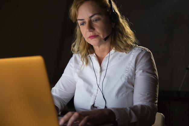 Trabajador serio de call center en auriculares