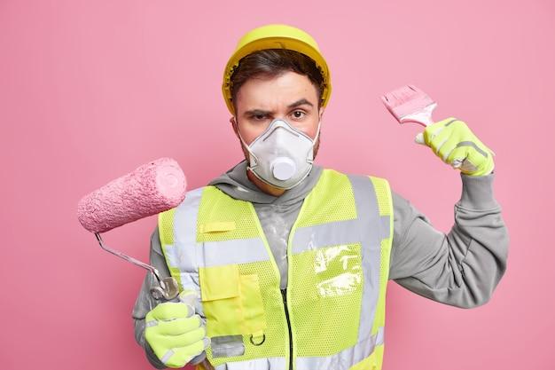 El trabajador serio del constructor sostiene el rodillo de pintura y el cepillo usa el uniforme de la máscara protectora del casco trabaja en la reparación de las poses de la nueva casa contra la pared rosada. renovación y reconstrucción de edificios
