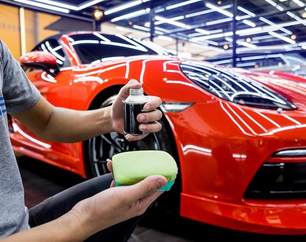 Trabajador de servicio automotriz aplicando nano revestimiento en el detalle de un automóvil