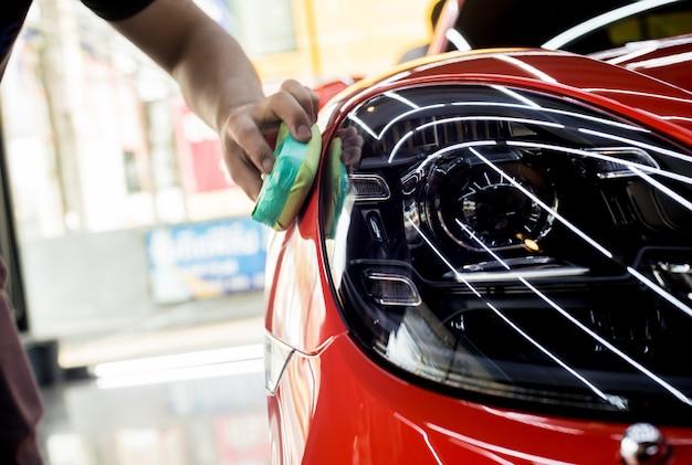 Trabajador de servicio de automóviles aplicando nano revestimiento en el detalle de un automóvil