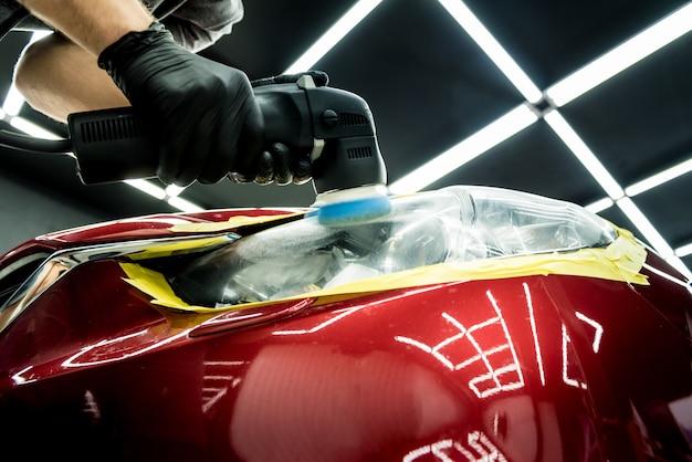 El trabajador del servicio de automóviles pule los detalles de un automóvil con un pulidor orbital.