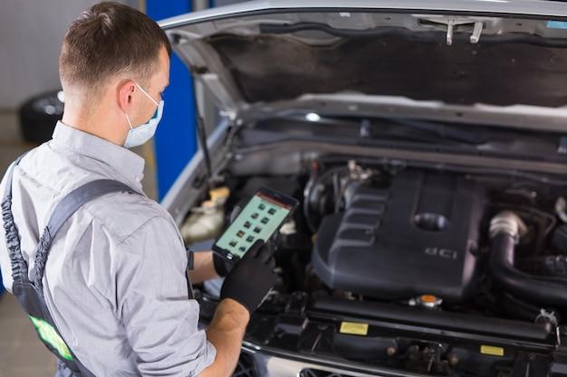 El trabajador de servicio de automóviles realiza diagnósticos y reparaciones de automóviles en la habitación.