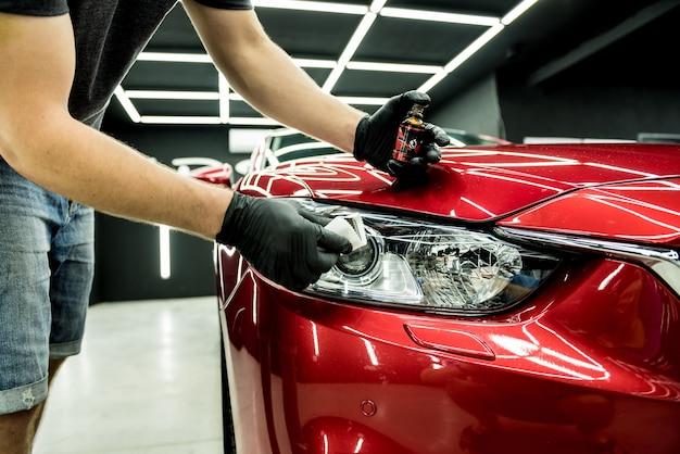 Trabajador de servicio de coche aplicando nano revestimiento en un detalle de coche.