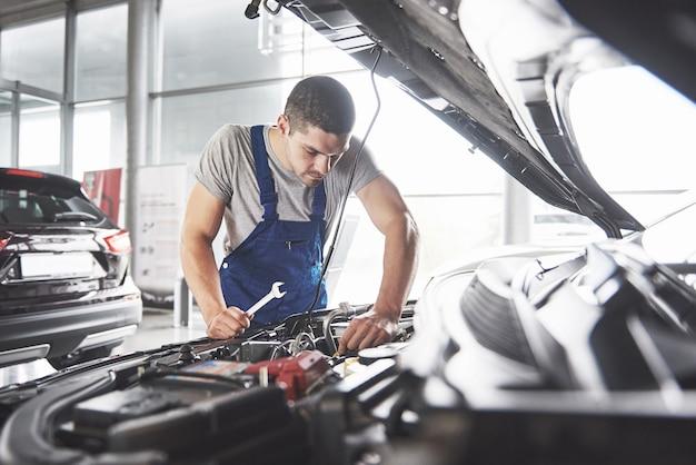 Trabajador de servicio de coche musculoso reparando vehículo.