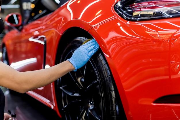Trabajador de servicio de coche pulido de ruedas de coche con tela de microfibra.
