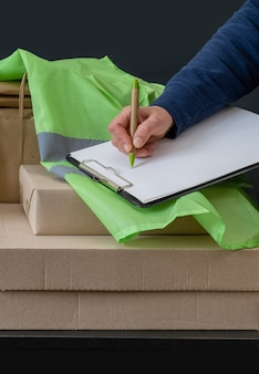 El trabajador del servicio de entrega permanece cerca del lugar de trabajo con cajas y escribe en tableta.