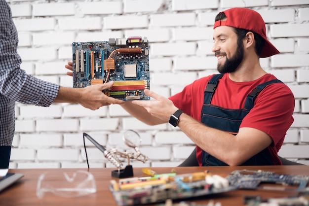 Trabajador del servicio informático recibe una placa base.