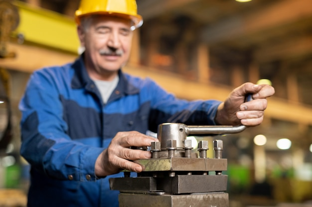 Trabajador de servicio de máquina industrial profesional senior manija giratoria del generador de hierro durante el trabajo en la fábrica