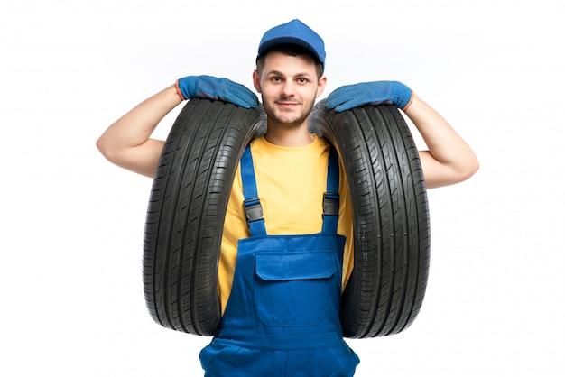 Trabajador de servicio de neumáticos en uniforme azul tiene neumático de coche