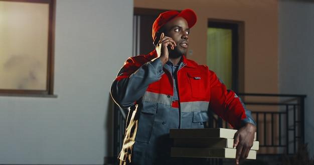 Trabajador de sexo masculino afroamericano de la entrega de pizza en el uniforme rojo y gorra de pie en la casa por la noche con cajas de pizza y hablando por el teléfono móvil. al aire libre.