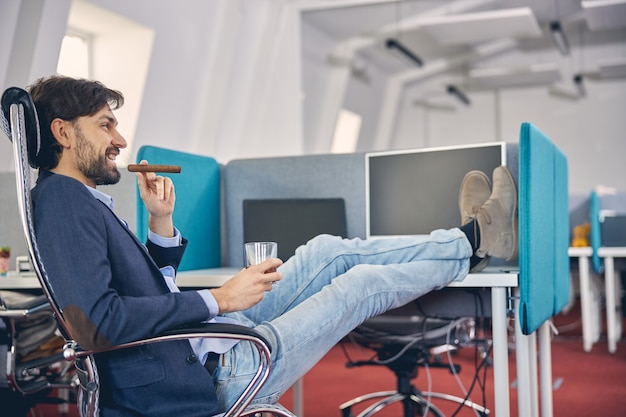 Trabajador de sexo masculino alegre sosteniendo un vaso de bebida alcohólica y sonriendo mientras disfruta de un cigarro en la oficina