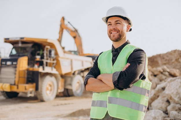Trabajador de sexo masculino con bulldozer en cantera de arena