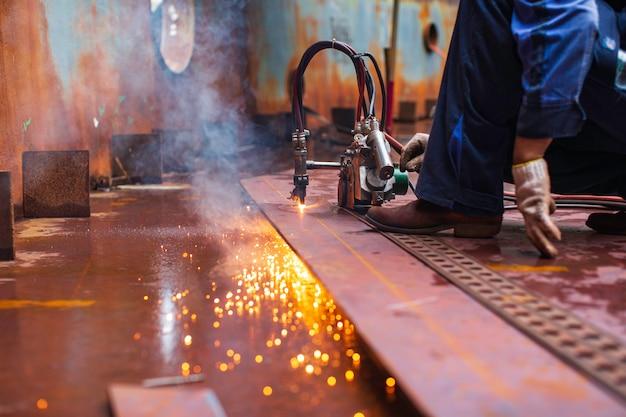 Trabajador de sexo masculino chispa de corte de metal en la placa de acero del fondo del tanque con destello de luz de corte de cerca en el espacio confinado lateral.