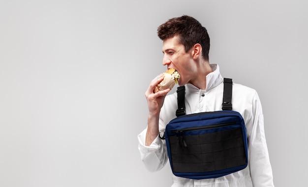 El trabajador de sexo masculino elegante joven con el bolso de aparejo del pecho está comiendo una hamburguesa jugosa sabrosa en un fondo blanco
