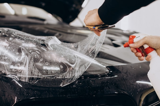 Trabajador de sexo masculino envolver el coche con lámina protectora