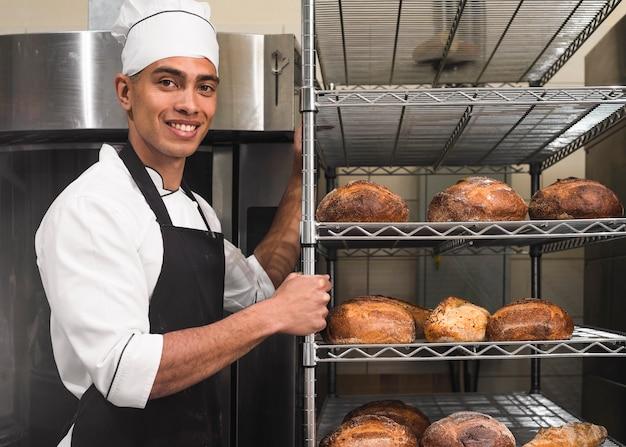 Trabajador de sexo masculino hermoso en uniforme que lleva estantes con la barra de pan en la panadería