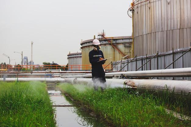 Trabajador de sexo masculino inspección visual de la oxidación de la corrosión del gas y el petróleo de la tubería a través del tubo de conexión de la tubería de escape de gas de vapor en el aislamiento.