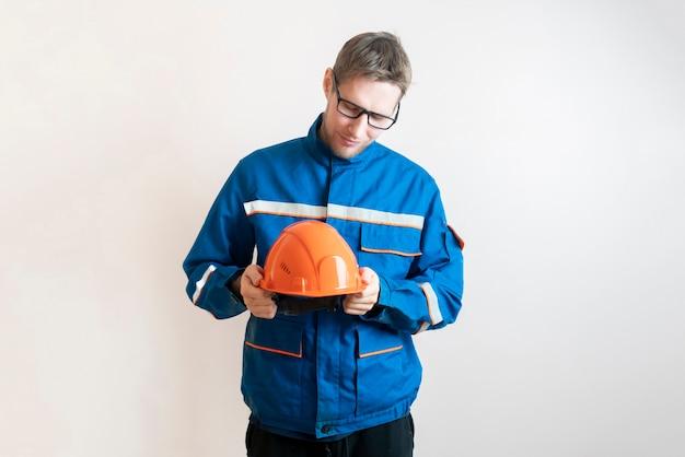 Trabajador de sexo masculino joven que sostiene un casco, equipo de seguridad industrial