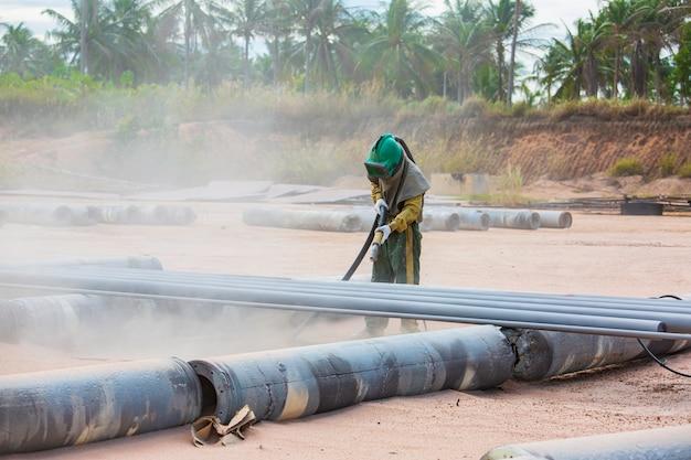 Trabajador de sexo masculino proceso de chorro de arena limpieza de la superficie de la tubería de acero antes de pintar en la fábrica.