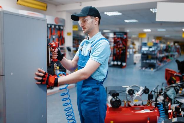 Trabajador de sexo masculino en la prueba uniforme de la clavadora neumática en el almacén de herramientas. elección de equipos profesionales en ferretería, supermercado de instrumentos