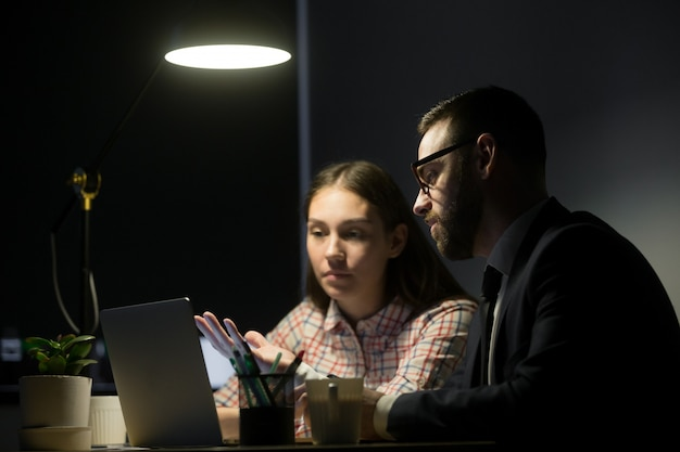 Trabajador de sexo masculino que explica planes de comercialización a la compañera de trabajo