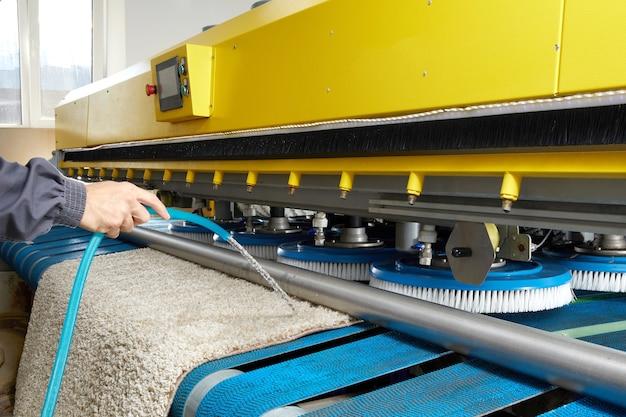 Trabajador de sexo masculino que limpia la alfombra en el equipo de la lavadora automática y el secador en el lavadero. servicio de lavado profesional