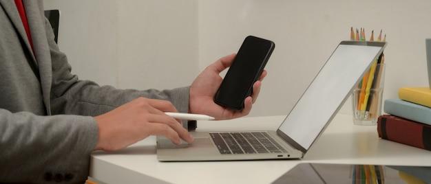 Trabajador de sexo masculino que trabaja con simulacro portátil y teléfono inteligente en la mesa de trabajo con suministros