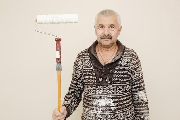 Trabajador de sexo masculino con rodillo de pintura pintando la pared blanca