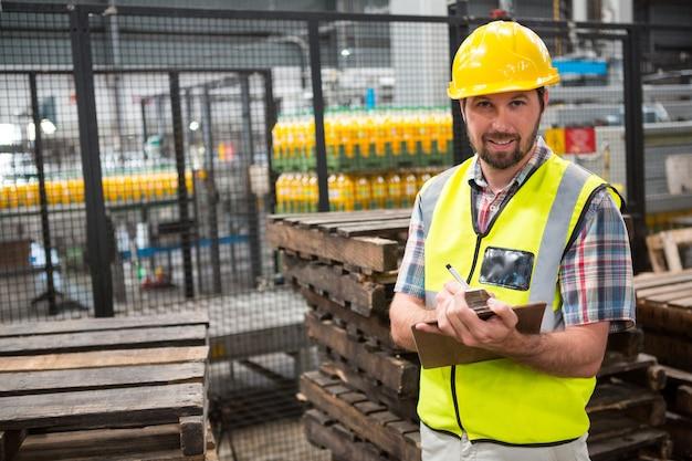 Trabajador de sexo masculino sonriente señalando acerca de los productos en el almacén