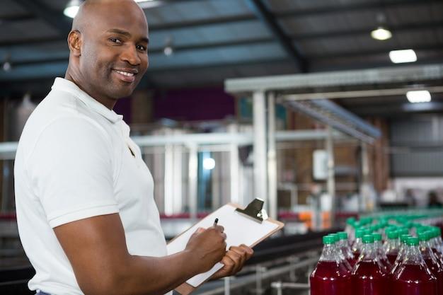 Trabajador de sexo masculino sonriente señalando acerca de productos en la fábrica de jugos