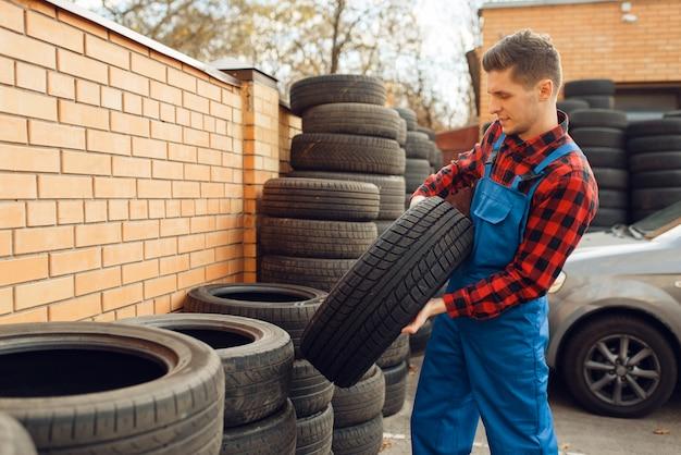 Trabajador de sexo masculino en uniforme en la pila de neumáticos, servicio de neumáticos.