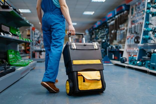 Trabajador de sexo masculino en uniforme tiene caja de herramientas sobre ruedas en tienda de herramientas. elección de equipos profesionales en ferretería, supermercado de instrumentos
