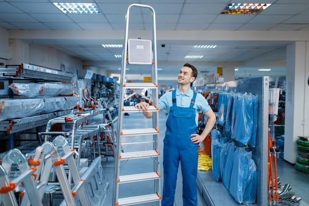 Trabajador de sexo masculino en uniforme tiene nuevas escaleras de tijera de aluminio en almacén de herramientas. departamento con escaleras, elección de equipo en ferretería, supermercado de instrumentos