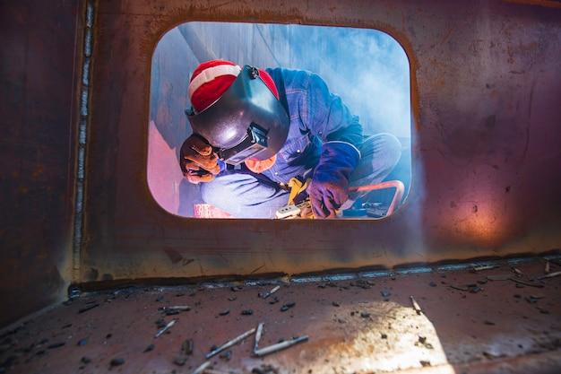 Trabajador de sexo masculino vistiendo ropa protectora y reparación de pozos de pontón de soldadura de humo de construcción industrial tanque de almacenamiento de flotador de aceite dentro de espacios confinados.