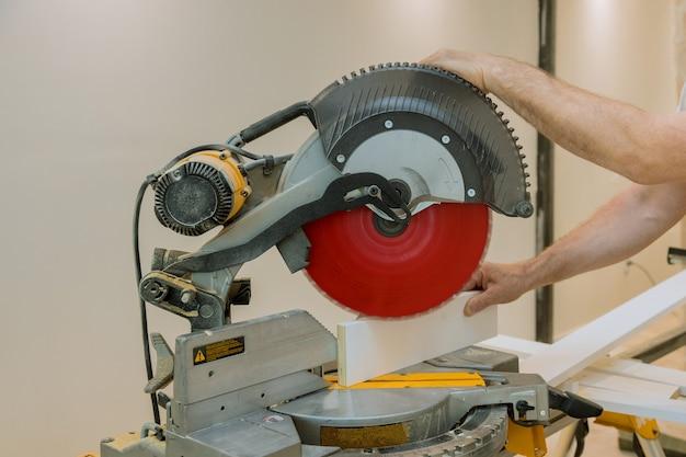 Un trabajador sierra ircular cortando una placa de moldura de madera en una construcción