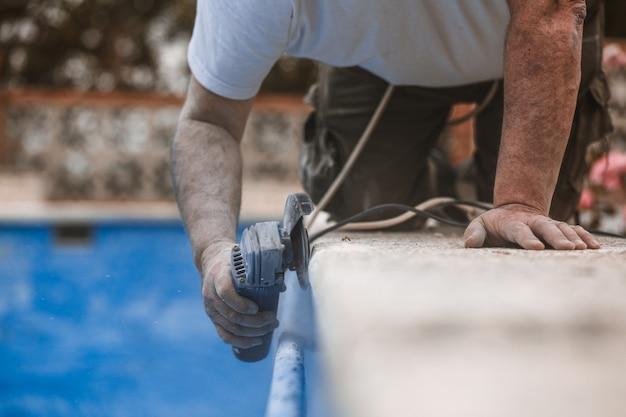 Trabajador con sierra radial con polvo en el aire con fondo azul