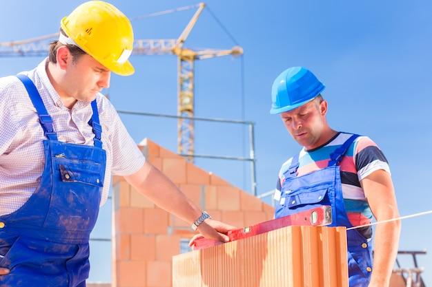 Trabajador del sitio de construcción o albañil con cascos controlando paredes con un nivel de burbuja o edificio o colocación o albañilería de pared en edificio