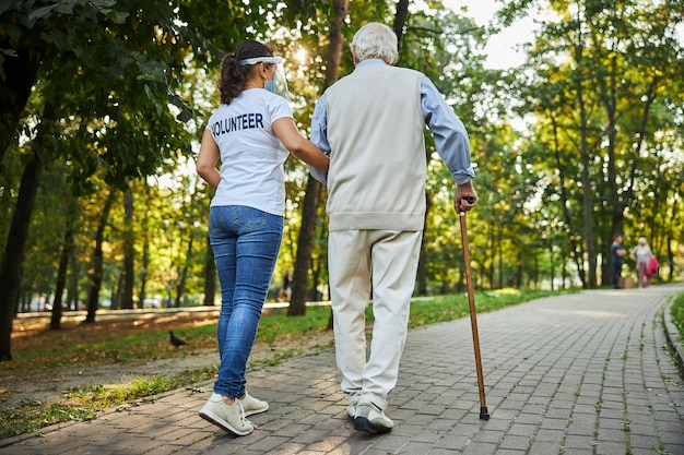 Trabajador social alegre en camisa blanca caminando con anciano en la calle