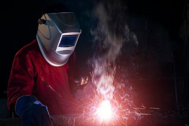 Trabajador de soldadura de una parte de metal en taller de soldadura industrial con iluminación de soldadura