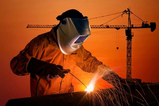 Trabajador de la soldadura que suelda la estructura de acero en el emplazamiento de la obra